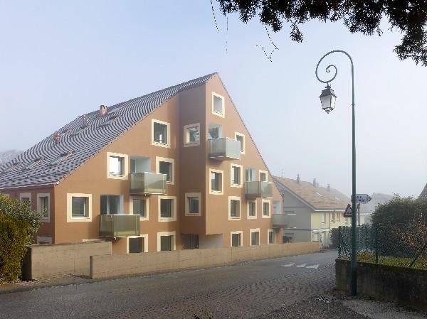 IMMEUBLE D&#039;HABITATIONS, Genolier<br /> <br /> FR.<br /> Le site se trouve au centre du village de Genolier, sur la rue de la gare, bord&eacute;e de murs d'enceinte et de maisons contigu&euml;s dont  les fa&ccedil;ades cr&eacute;pies, l'orientation des toitures propre &agrave; chacune, sont issues d'une architecture vernaculaire et traditionnelle, et font le charme du village.<br /> <br /> Le projet poursuit le front de rue avec un mur d'enceinte cr&eacute;ant une cour int&eacute;rieure devant l'entr&eacute;e. C'est le nouvel espace d&#039;accueil et de rencontre. Il est min&eacute;ral, g&eacute;om&eacute;trique et &agrave; destination publique. Derri&egrave;re ce mur, on voit appara&icirc;tre la maison avec sa fa&ccedil;ade en cr&eacute;pi min&eacute;ral et ses fen&ecirc;tres aux dispositions variables, reprenant l'image des maisons villageoises. Le sens de la toiture donne une image d'unit&eacute; depuis la route avec les maisons voisines et valorise l'orientation nord sud avec ses deux ambiances distinctes : au sud, la cour d'entr&eacute;e et au nord, le jardin paysager. Sur le c&ocirc;t&eacute;, une rampe permet d'acc&eacute;der &agrave; ce jardin en l&eacute;g&egrave;re pente, qui m&egrave;ne &agrave; la for&ecirc;t et &agrave; son ruisseau. Le parc est am&eacute;nag&eacute; d'un espace de d&eacute;tente pour les r&eacute;sidents de l'immeuble.<br /> <br /> Le volume comprend 14 logements pour des jeunes couples ou des personnes &acirc;g&eacute;es. Sur un &eacute;tage type, on trouve quatre appartements de 3.5 pi&egrave;ces. Chacun est plac&eacute; sur un des quatre angles du volume, ce qui permet d'offrir une double orientation du logement. La relation int&eacute;rieur/ext&eacute;rieur est renforc&eacute;e gr&acirc;ce &agrave; des balcons-loggias. Les sanitaires se superposent rationnellement au centre du b&acirc;timent afin de lib&eacute;rer un maximum de surface pour les espaces de vie et les chambres. Les fen&ecirc;tres, toutes carr&eacute;es, sont sign