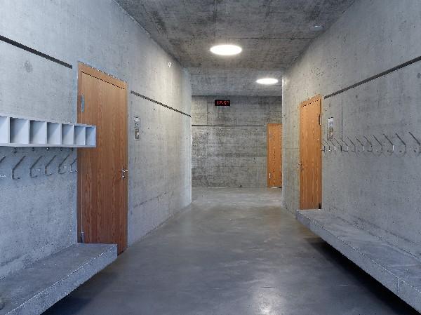 ECOLE PRIMAIRE, Voll&egrave;ges<br /> <br /> FR.<br /> Le nouveau b&acirc;timent scolaire s'implante &agrave; l'ouest de la parcelle constructible, cr&eacute;ant avec le b&acirc;timent de la salle polyvalente un complexe scolaire avec comme centre, la cour d'&eacute;cole. De cette place libre de tout v&eacute;hicule, on acc&egrave;de aux divers b&acirc;timents du site : la salle de gymnastique polyvalente, l'&eacute;cole primaire et la cantine du football.<br /> Un espace couvert en bordure de la place fait office de pr&eacute;au et permet de relier l'&eacute;cole &agrave; la salle de gym. On y trouve un escalier qui m&egrave;ne &agrave; la partie sup&eacute;rieure en relation avec les transports publics. Cette d&eacute;limitation claire des fonctions permet de garantir une s&eacute;curit&eacute; des utilisateurs ainsi qu'un fonctionnement optimal des installations.<br />  <br /> Le b&acirc;timent principal s'organise sur trois &eacute;tages. Les quatre salles de classes par niveau sont situ&eacute;es dans les angles et disposent chacune d'une double orientation. A l&#039;est, au niveau de la cour d'&eacute;cole, la cantine prend place sous la place de stationnement des cars et est directement en liaison avec la cuisine de la salle polyvalente. Cet espace est disponible soit pour l'&eacute;cole soit pour le club de foot. Un passage traversant permet de relier le terrain de foot &agrave; la cour d'&eacute;cole et ainsi le faire participer &agrave; la vie du complexe.<br /> <br /> Les fa&ccedil;ades sont r&eacute;alis&eacute;es en b&eacute;ton pour reprendre le langage de la salle polyvalente et unifier les diff&eacute;rentes parties du complexe. Elles sont trait&eacute;es de mani&egrave;re 'plastique' avec des biais en fa&ccedil;ade. Les couloirs en b&eacute;ton brut sont la prolongation des espaces ext&eacute;rieurs et contrastent avec les classes qui elles sont trait&eacute;es de mani&egrave;re plus chaleureuses avec des panneaux en m&eacute;l&egrave;ze et des coul